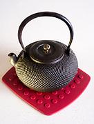 Japanese iron tea kettle on silicon hot pad.
