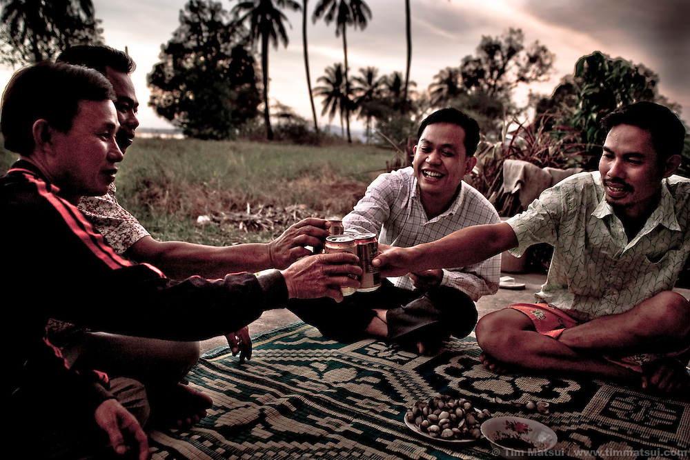 Immigration police and other local residents, including Mr. Dara who works with the Cambodian non governmental organization Healthcare Center for Children, which works against exploitation and human trafficking, get drunk at the end of the day on the old royal palace grounds in Koh Kong near the border with Thailand.