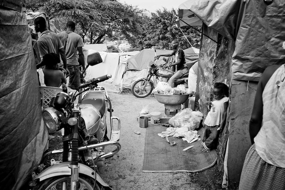 A man rides a motorcycle through a tent camp for people displaced by the earthquake on February 21, 2010 in Petionville, outside Port-au-Prince, Haiti.