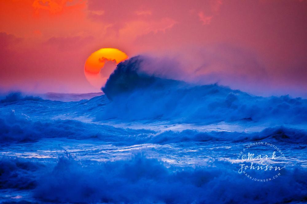 Kauai, Hawaii, USA --- The setting sun and large winter waves breaking off the north coast of Kauai, Hawaii