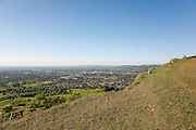 A couple admire the view over Cheltenham Spa town at the top of cliffs at Leckhampton Hill, Gloucestershire