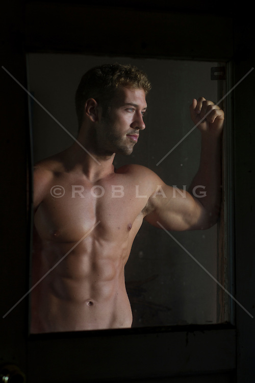 shirtless man looking out a window