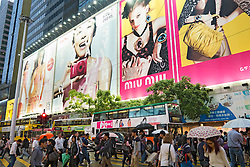 People crossing busy street with billboards to rear in Causeway Bay Hong Kong