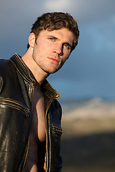 rugged man in a leather jacket and no shirt