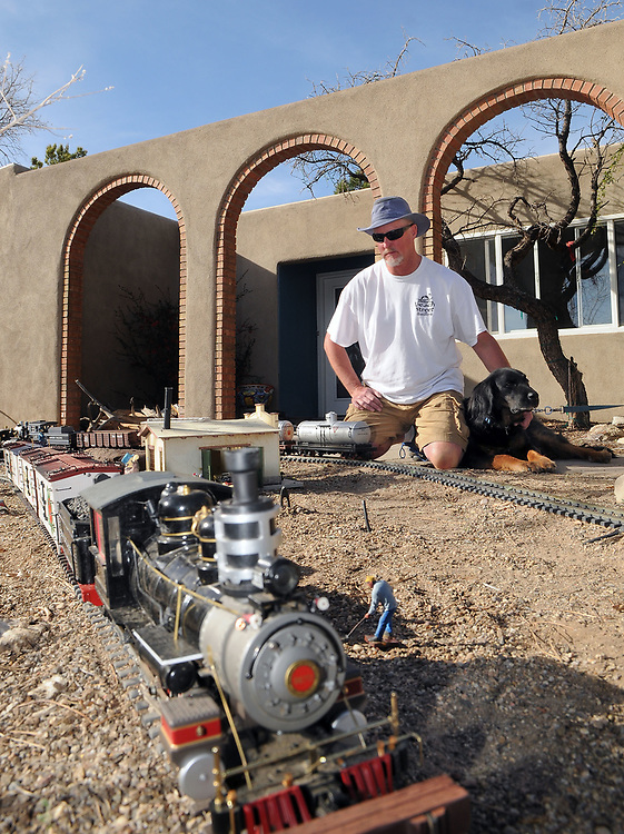 jt031517i/spec sec/jim thompson/ Rick Hill, president of the New Mexico Garden Railroad Club with his dog Reggie watches as the trains runs it's course in his front yard.   Wednesday Feb. 15, 2017. (Jim Thompson/Albuquerque Journal)