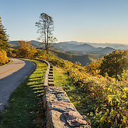 See a lovely sunset view of the Blue Ridge Mountains (a subset of the Appalachian Mountains) at Chimney Rock Mountain Overlook (Milepost 44.9, elevation 2485 feet) on the Blue Ridge Parkway, near Buena Vista, Virginia, USA. Local trees release hydrocarbons into the atmosphere and create a characteristic blue haze on pristine days as seen in this photo; but more often a white or gray haze obscures distant views due to air pollution. The scenic 469-mile Blue Ridge Parkway connects Shenandoah National Park (in Virginia) with Great Smoky Mountains National Park in North Carolina, following crestlines and the Appalachian Trail. This panorama was stitched from 3 overlapping photos.