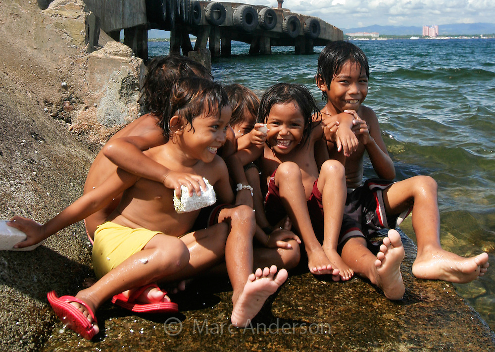 A group of young children sitting by the sea & playing together, Olango Island, Cebu, Philippines