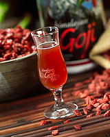 Himalayan Goji juice in a branded glass, shot on bamboo sticks with goji fruit surrounding it.