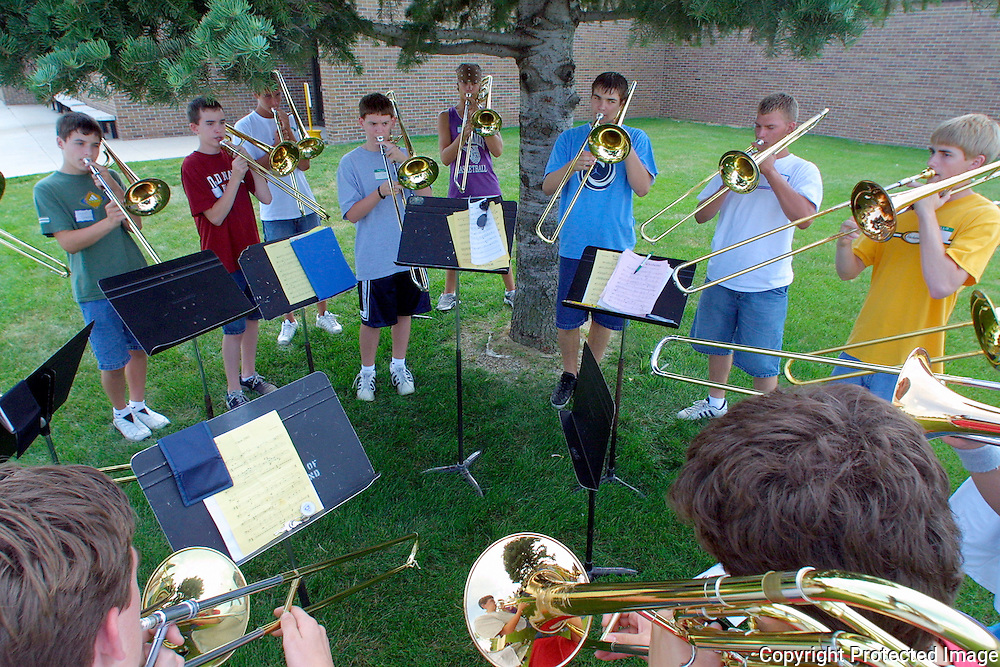 """The trombone section of the MOC-Floyd Valley band seek relief from the August heat by practicing  under the shade of a pine tree during band camp in Orange City during the  summer.  """"There are bands all over the state rehearsing right now with one goal in mind - defeat the Pride of the Dutchmen Marching Band in competition this year,"""" said band director Steve Connell."""