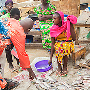 LÉGENDE: Des clients marchandent avec Rosine sur le prix de poissons. LIEU: Marché de Chagoua, N'Djaména, Tchad. PERSONNE(S): Rosine Remadsi au milieu et à gauche des clients. En arrière plan: Une femme vendeuse assit.