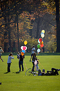 Two groups multi colored helium balloons over Sheep Meadow.