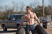 shirtless automobile handyman carrying tires