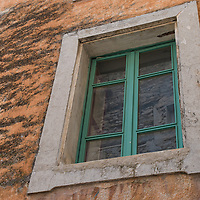 Green window on an terra cotta colored wall in Gordes.