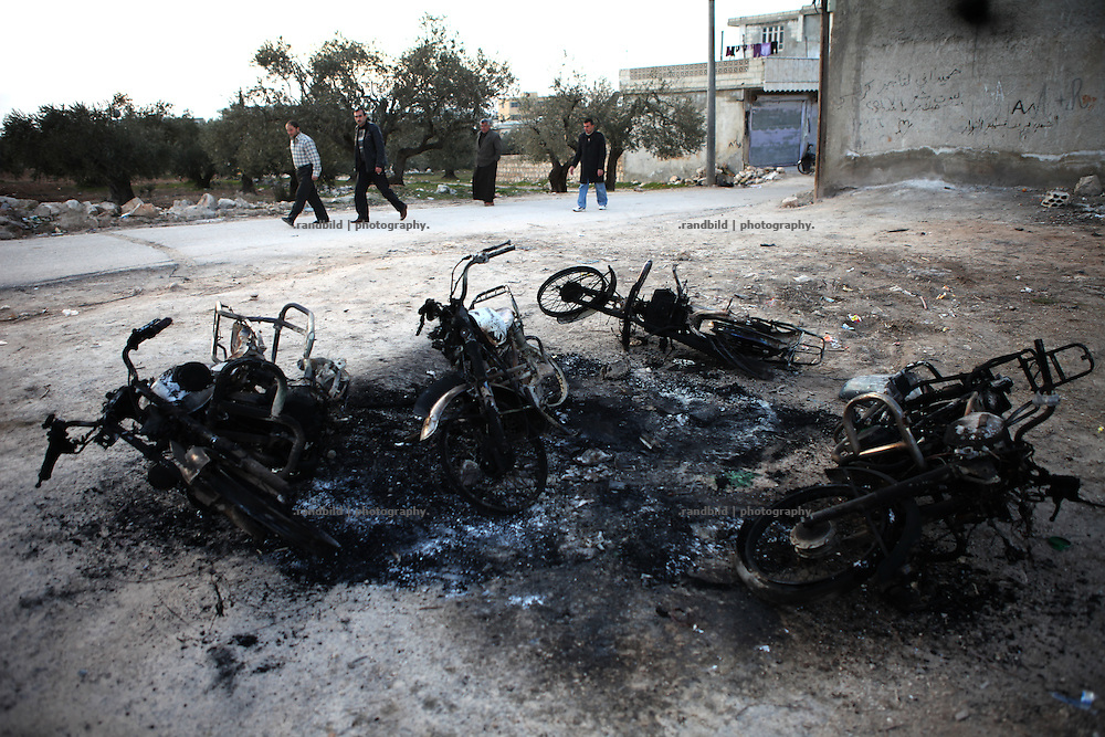 Burnt motorcycles in the streets of Kureen. On 22. February the syrian army attacked the village of Kureen, Province of Idlib, Syria. Kureen was among the first villages in the northwest of Syria controlled by the opposition. Some villagers and members of the defence units escaped to surrounding olive orchards, when the attack begun in the early morning. A majority of the inhabitants didn´t manage to escape. The heavy shelling lasts 7 houres. Soldiers searched all houses, burnt some of them down, loote shops, stole cars and furniture. About 60 motorcycles were burnt down. Tanks demolished several houses. 6 men were executed. One woman died as a result of an heart attack.