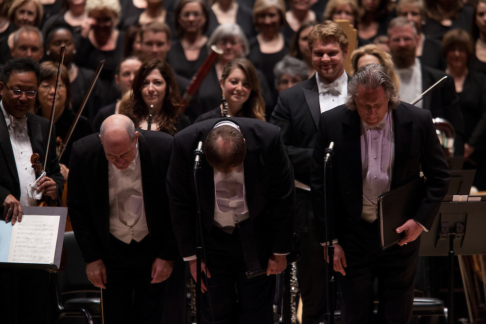 Music Director and Conductor Robert Spano, left, with Tenor Thomas Cooley and Baritone Stephen Powell, right, bows to the audience with the Atlanta Symphony Orchestra and Chorus performing Benjamin Britten's War of Requiem at Carnegie Hall in New York, NY on April 30, 2014.