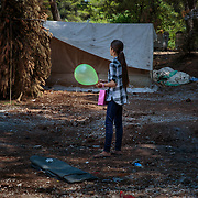 A young refugee from Aleppo, Syria holds her Eid Al Fitr balloon and gift bag distributed by an INGO in Ritsona refugee camp, an hour north of Athens, Greece.<br /> <br /> The Balkan borders were closed to refugees in March 2016. According to the IRC, as of April 2017 62,000 refugees are stranded in Greece.