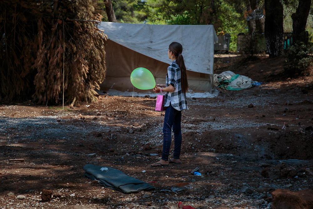 A young refugee from Aleppo, Syria holds her Eid Al Fitr balloon and gift bag distributed by an INGO in Ritsona refugee camp, an hour north of Athens, Greece.<br />
