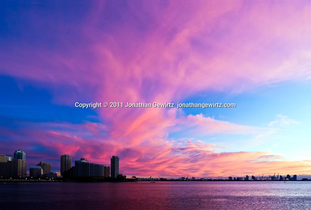 The warm light of the rising sun dramatically tints clouds over the Port of Miami, Florida. WATERMARKS WILL NOT APPEAR ON PRINTS OR LICENSED IMAGES.