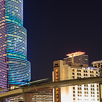 A Miami Metromover automated rail car crosses the Miami River at night in front of the Miami Tower.