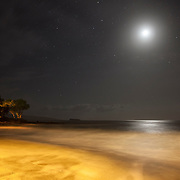 The moon shines over the golden Makena Beach on the Hawaiian island of Maui at night.