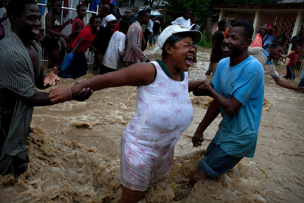 After hurricane Tomas went through Haiti, the city of Leogane has been totally flooded by the heavy rain and the overflow of the river Roullorne.///A Haitian woman tries to go out of the the muddy water with the help of her friends, in a street of Leogane during hurricane Tomas.