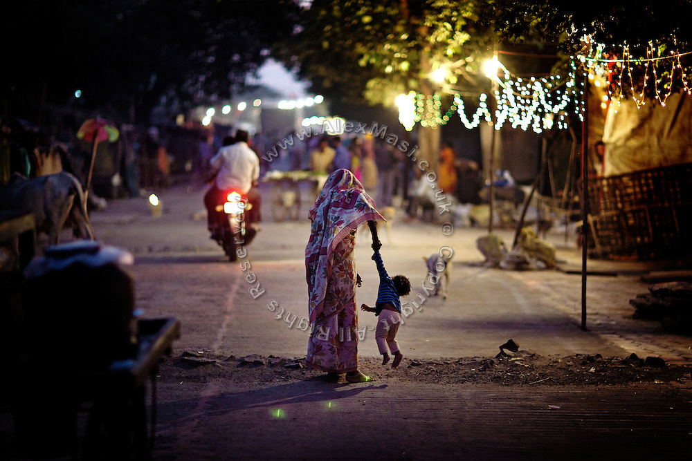A woman is lifting her child on the streets of Oriya Basti, one of the water-affected colonies surrounding the abandoned Union Carbide (now DOW Chemical) industrial complex in Bhopal, Madhya Pradesh, India, site of the infamous 1984 gas tragedy. The poisonous cloud that enveloped Bhopal left everlasting consequences that today continue to consume people's lives.