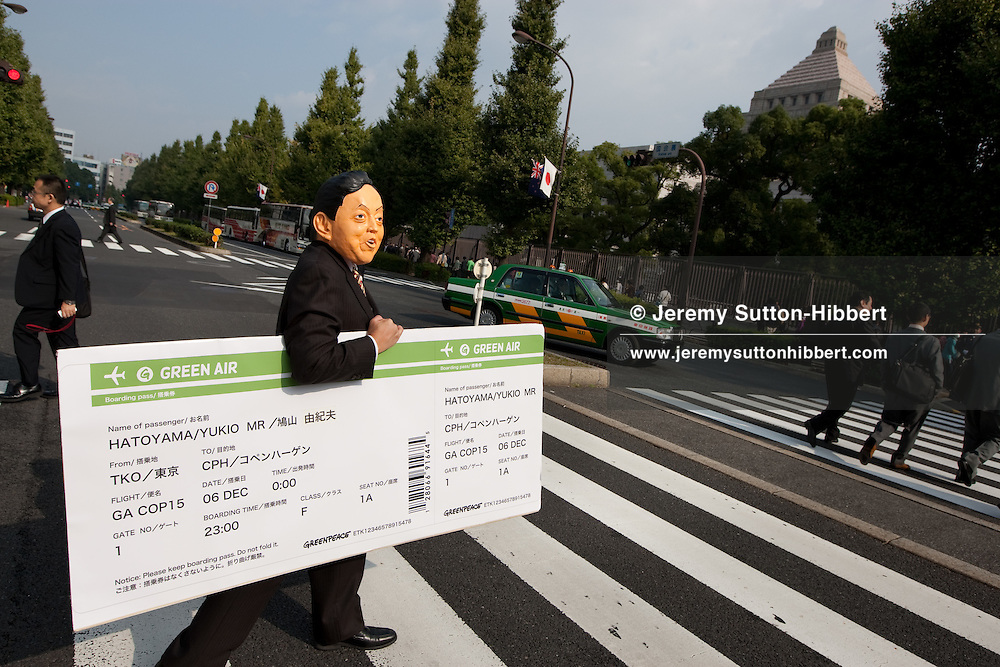Outside the Japanese National Diet Assembly building, Thomas Henningsen - GPI Copenhagen Climate Change meeting project leader, hands a mock plane ticket to an impersonator of Yukio Hatoyama, Prime Minister of Japan, as he urges the Prime Minister to show further strong leadership by attending the climate change meeeting in Copenhagen, Denmark in December. Tokyo, Japan, Thursday 29th October 2009.  Greenpeace Japan ran a cyber action to collect signatures of those who would like to ask Prime Minister Hatoyama to go to Copenhagen and to urge his fellow governemntal leaders to follow his strong leadership, the petition of signatures and names was handed today to a secretary of the Prime Ministers office by representatives of Greenpeace Japan and Greenpeace International.