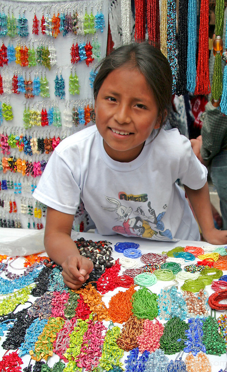 South America, Ecuador, Otavalo.  Young girl sells her handmade jewelry at the Otavalo Market in the Andes of Ecuador.
