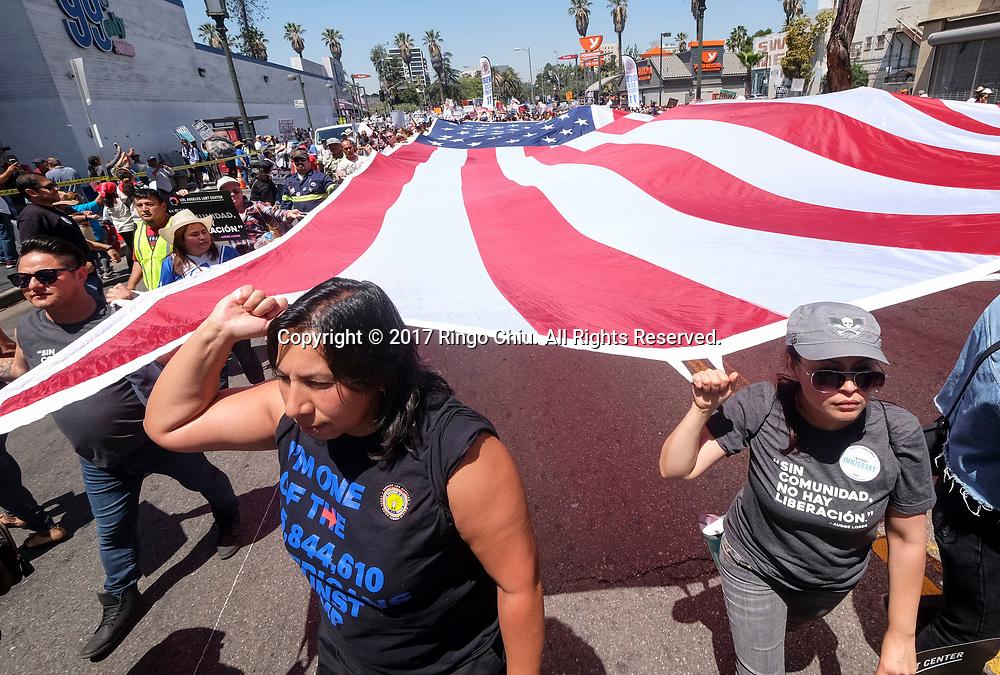 5月1日,在美国洛杉矶,人们手持标语牌参加&ldquo;五一&rdquo;国际劳动节游行。 当日,全美各城市的数以万计移民及其支持者集会抗议特朗普总统的移民政策,为工人权益发声。新华社发(赵汉荣摄)<br /> Protesters carry a giant U.S. flag marching toward downtown Los Angeles in the annual May Day March in Los Angeles, the United States, May 1, 2017. Thousands of people took to the streets across the nation Monday to march in May Day rallies, calling for immigration reform, workers' rights and police accountability. (Xinhua/Zhao Hanrong)(Photo by Ringo Chiu/PHOTOFORMULA.com)<br /> <br /> Usage Notes: This content is intended for editorial use only. For other uses, additional clearances may be required.