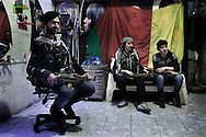 """SYRIA, ALEPPO : Kurdish fighters from the """"Popular Protection Units"""" (YPG) sit in their headquarter (former hair salon) in the majority-Kurdish Sheikh Maqsud district of the northern Syrian city of Aleppo, on April 16, 2013. ALESSIO ROMENZI"""