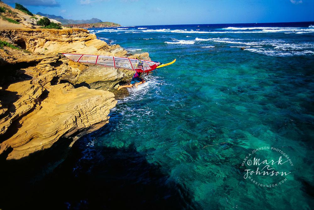Windsurfer jumping off cliff to go Windsurfing - Kauai, HI