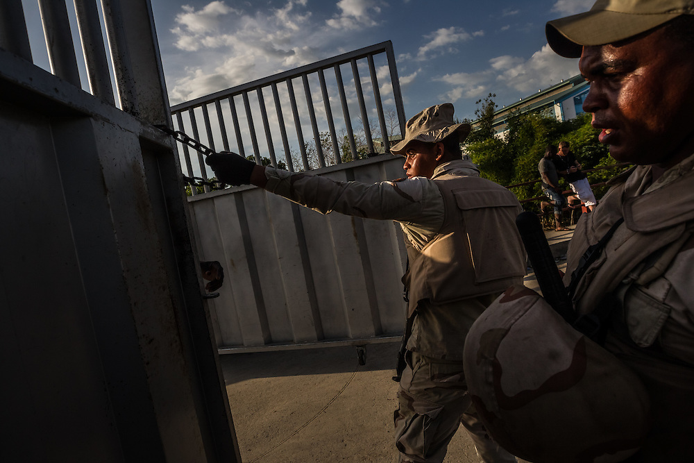 DAJABÓN, DOMINICAN REPUBLIC - JUNE 26, 2015: Border guards work to shut down the border by closing the gate that separates Haiti and the Dominican Republic. PHOTO: Meridith Kohut for The New York Times