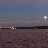The full moon rises over Miami harbor, Virginia Key, the Rickenbacker Causeway and the Port of Miami with Fisher Island and Miami Beach buildings in the background.<br />