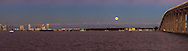 The full moon rises over Miami harbor, Virginia Key, the Rickenbacker Causeway and the Port of Miami with Fisher Island and Miami Beach buildings in the background.<br /> WATERMARKS WILL NOT APPEAR ON PRINTS OR LICENSED IMAGES.