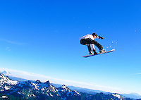Young man snowboarding, leaping in mid-air, profile