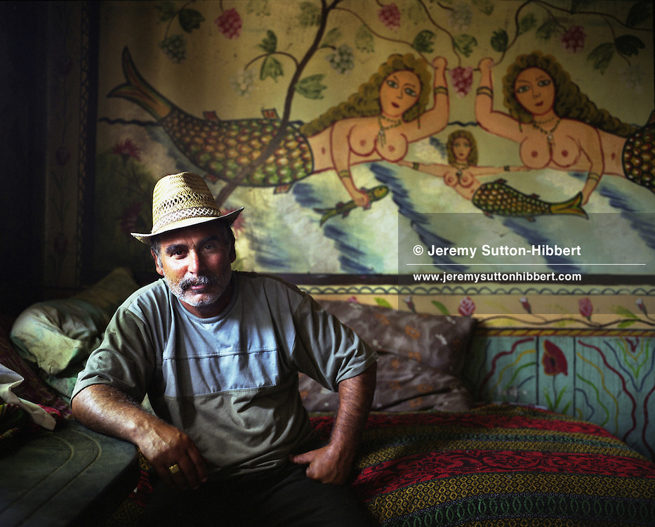 """A roma elder sits in front of a poorly painted mural depicting mermaids in a house in the """"old"""" part of the village of Sintesti, in Romania, early August 2006. The old part of the village houses the poorer families within the camp who have not yet earned enough money to move down nearer to the main road, and to build a new home. The Kalderari roma of Sintesti are by tradition metal workers, originally making alcohol stills, pots and pans, but now dealing in scrap metal. The large profits from their business have enabled them to build large houses in the village of Sintesti, 20km from Bucharest, and to invest in fast, Western brand name cars such as BMW's, Mercedes and Porsche."""