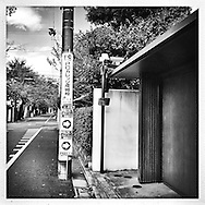 Security cameras for a condominium catch sight of me as I walk by on the way to the train station.  Tokyo, Japan.