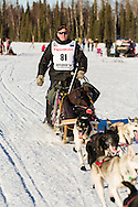 Musher Ken Anderson competing in the 44th Iditarod Trail Sled Dog Race on Long Lake after leaving the restart on Willow Lake in Southcentral Alaska.  Afternoon. Winter.