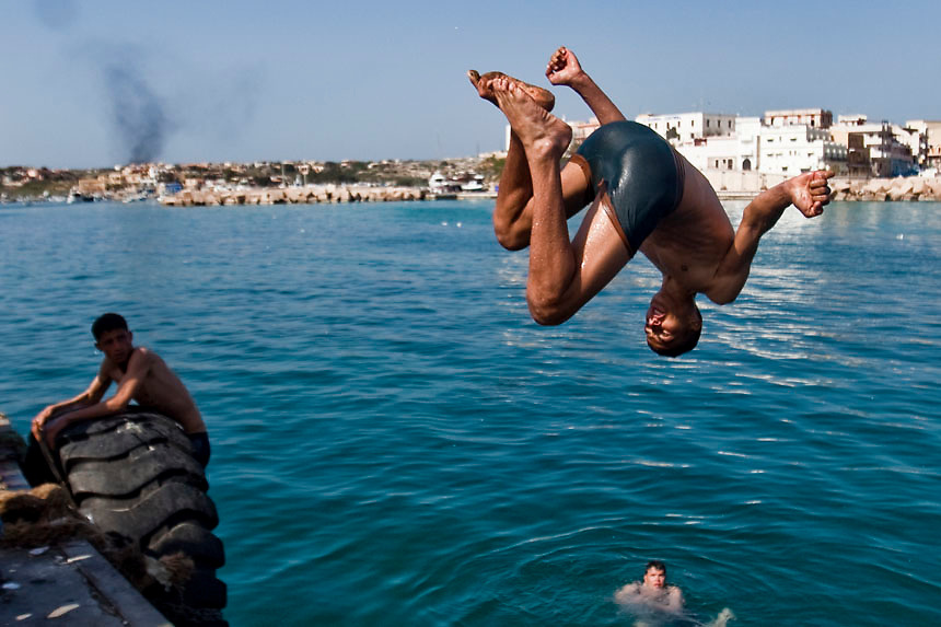 Northern African refugees refreshe themselves jumping into the sea in the portual area of the Lampedusa Island. Despite the efforts of italian government who evacuated more 600 northen african refugees yesterday by the S. Marco ship, boats continues to attrack in the Island the situation is worsening The portual area of Lampedusa has become a second open air immigration centre where immigrants live in critical igenic and sanitary conditions.
