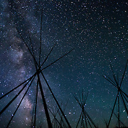 Tipi frames under a night sky from a Nez Perce encampment at Big Hole National Battlefield, Montana. The tipi frames represent the Nez Perce home and families that were present when the U.S. Military attacked at pre--dawn in 1877 killing many women and children. Nez Perce warriors put up a fierce resistance and held the Cavalry at bay for two days while their people re-grouped and retreated from the Big Hole Valley.