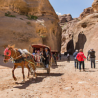 Jordan, Petra, Local horsemen drive carriages carrying foreign tourists on path leading to ancient ruins