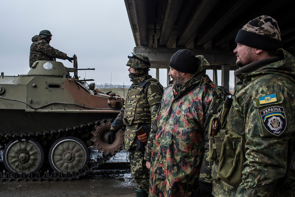 PERVOMAISKE, UKRAINE - NOVEMBER 19, 2014: Padre, second from right, watches the arrival of a Ukrainian army tracked armored personnel carrier with other members of the Dnipro-1 brigade, a pro-Ukraine militia, at their base under a bridge in Pervomaiske, Ukraine. CREDIT: Brendan Hoffman for The New York Times