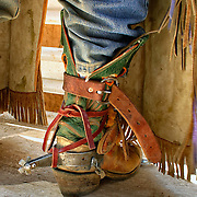 This is a rodeo cowboy and his spurs are designed to help him stay on a bucking bull. His chaps have long fringes for more flash during his ride. His boots are tied on to prevent them from coming off during the ride.