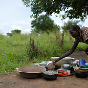 """Regina Libiriko in Kudo village in Eastern Equatoria, South Sudan on 8 August 2014. Due to a combination of drought in some parts of the country, the ravages of pests in others, and instability caused by war, many South Sudanese are facing acute food shortages and possibly famine. Regina says, """"I harvested 10 bundles of sorghum, and as I have six children, it will run out by the end of August. Then I will go to the bush and collect the leaves that we always eat, and prepare that for the children."""""""