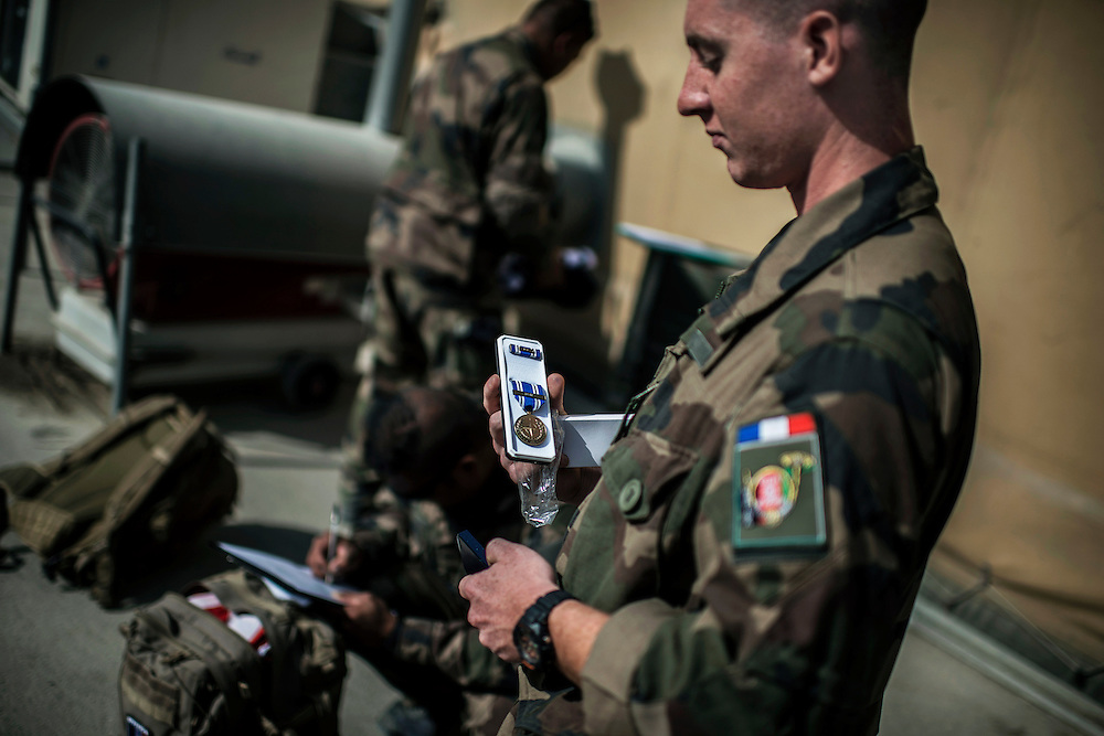 16th BC French unit soldier looks at the medal he received after his 5 months mission on September 29, 2012  in KAIA airport in Kabul. The French unit from Bitche (Moselle) spent a week disassembling weapons, cleanning tanks and preparing their departure for France. AFP PHOTO / JEFF PACHOUD