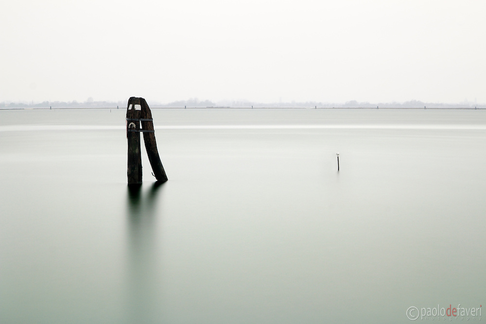 A briccola, the grouped poles used to mark the border of ship canals in the Venetian lagoon. Taken from the small harbour of Burano on an rainy evening at the beginning of February
