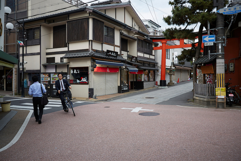A salaryman on a bicycle rides past another on foot in a scene that plays out everyday across Japan.