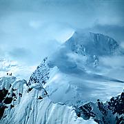 Three climbers sihouetted on a ridge of Mount Dickey in the Alaska Range near Mount McKinley.