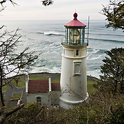 Heceta Head Lighthouse, on the Oregon coast, USA.. Heceta Head Lighthouse may be the most photographed beacon in the United States. Built in 1893, it was named for the Spanish mariner who is credited with being the first European to set foot in the region. The light at top of 56-foot tower was first illuminated in 1894. Perched 205 feet above the ocean, its fresnel lens beams the brightest light on the Oregon coast, visible up to 21 miles out to sea. Location: Halfway between Cape Perpetua and Florence, a turnoff just south of Carl Washburne State Park (which has a great campground) takes you to the parking lot on a beach, where you can walk a half mile to the lighthouse. Heceta Head State Park includes Devils Elbow State Park and is located in a scenic cove at the mouth of Cape Creek.