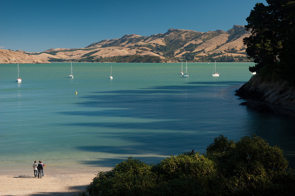 People on a sunny beach at Corsair Bay, Lyttelton Harbour, New Zealand, look at yachts and boats moored in shaded shallow water